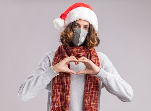 Giovane che indossa il cappello di babbo natale e la maschera protettiva per il viso con una sciarpa calda intorno al collo che fa il gesto del cuore con le dita