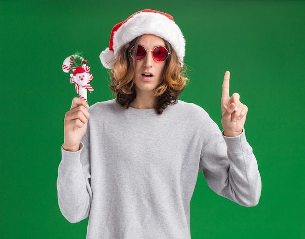 Young man wearing christmas santa hat and red glasses holding christmas candy cane looking at camera surprised showing index finger having new idea standing over green background