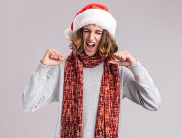 首に暖かいスカーフをかぶったクリスマスサンタの帽子をかぶった若い男は、白い壁の上に立って狂った幸せで興奮した拳を握り締めます