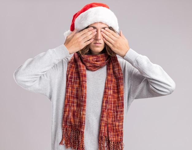 白い壁の上に立っている手で目を覆っている彼の首の周りに暖かいスカーフとクリスマスサンタの帽子をかぶっている若い男