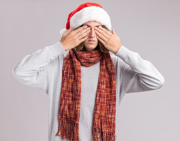 Young man wearing christmas santa hat with warm scarf around his neck covering eyes with hands standing over white  wall