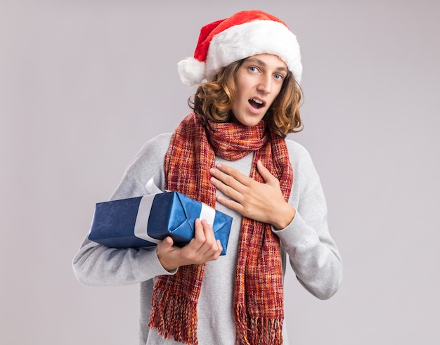 Young man wearing christmas santa hat with warm scarf around his neck holding christmas present looking surprised feeling thankful standing over white  wall