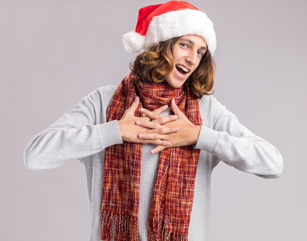 그의 가슴에 손을 잡고 그의 목에 따뜻한 스카프와 함께 크리스마스 산타 모자를 쓰고 젊은 남자가 흰 벽 위에 행복하고 밝은 미소 서