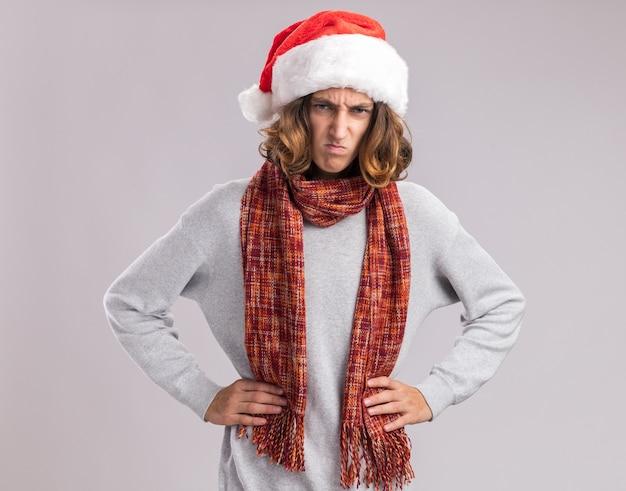 白い壁の上に立っている腰に腕と怒っている眉をひそめている顔と彼の首の周りに暖かいスカーフとクリスマスサンタ帽子をかぶっている若い男