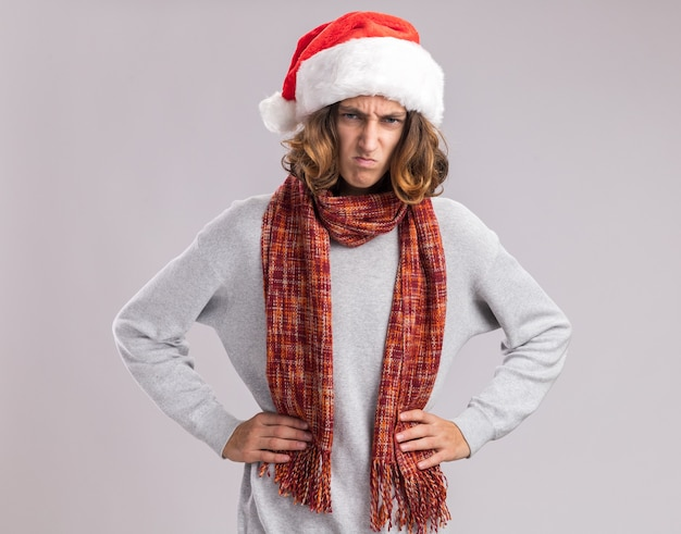 Young man wearing christmas santa hat with warm scarf around his neck  with angry frowning face with arms at hip standing over white  wall