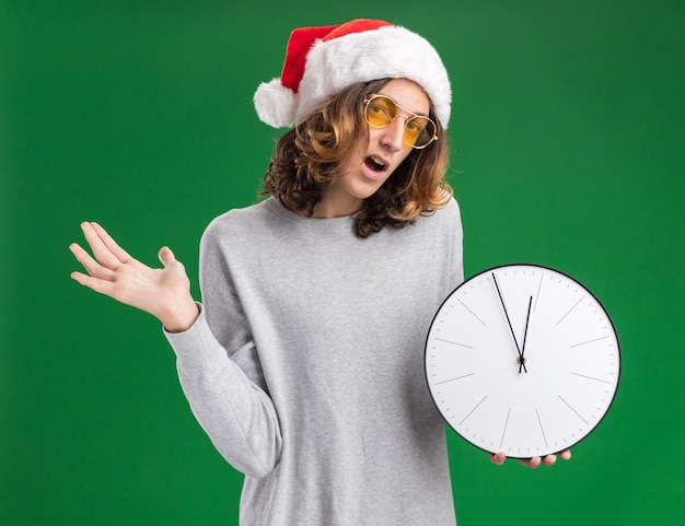 Giovane uomo che indossa il cappello di babbo natale e occhiali gialli che tengono l'orologio da parete sorpreso in piedi sul muro verde green