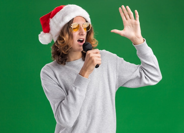 Young man wearing christmas santa hat and yellow glasses shouting to microphone with raised arm  standing over green wall