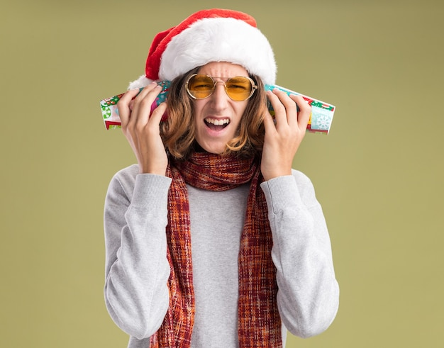 Young man wearing christmas santa hat and yellow glasses with warm scarf around his neck covering his ears with colorful paper cups with annoyed expression standing over green wall