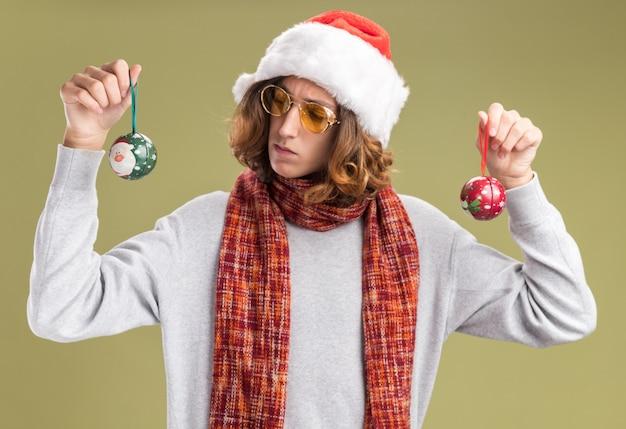 Giovane che indossa un cappello da babbo natale e occhiali gialli con una sciarpa calda intorno al collo con in mano le palle di natale che sembra confuso avendo dubbi in piedi sul muro verde