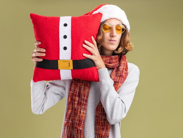 Young man wearing christmas santa hat and yellow glasses with warm scarf around his neck holding christmas pillow  with closed eyes feeling positive emotions standing over green wall