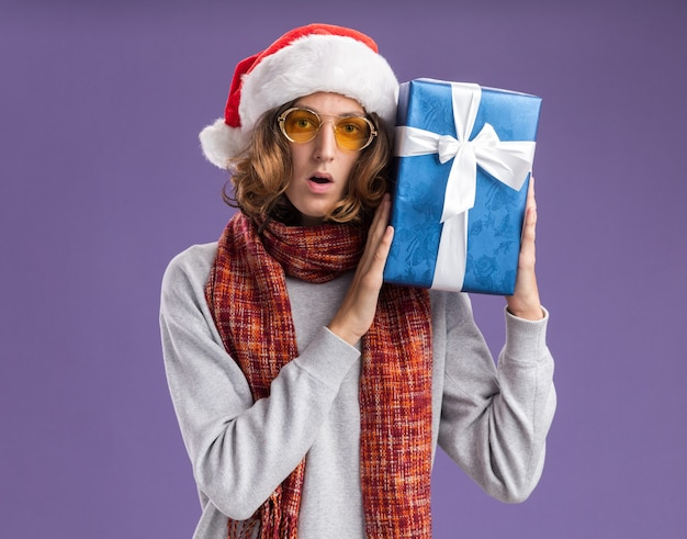 Young man wearing christmas santa hat and yellow glasses with warm scarf around his neck holding christmas present  surprised  standing over purple  wall