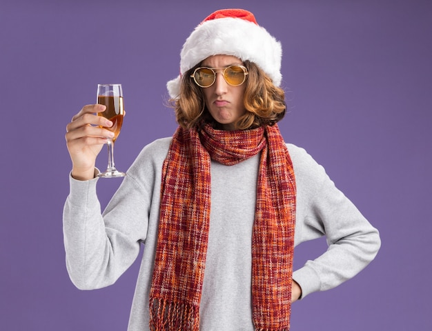 Young man wearing christmas santa hat and yellow glasses with warm scarf around his neck holding glass of champagne  looking at it puzzled standing over purple  wall