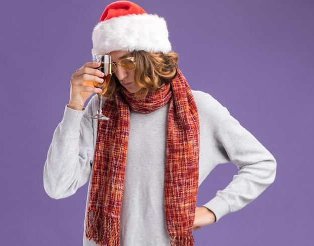 Giovane uomo che indossa natale santa hat e occhiali gialli con una calda sciarpa intorno al collo tenendo un bicchiere di champagne cercando stanco e annoiato depresso in piedi su sfondo viola