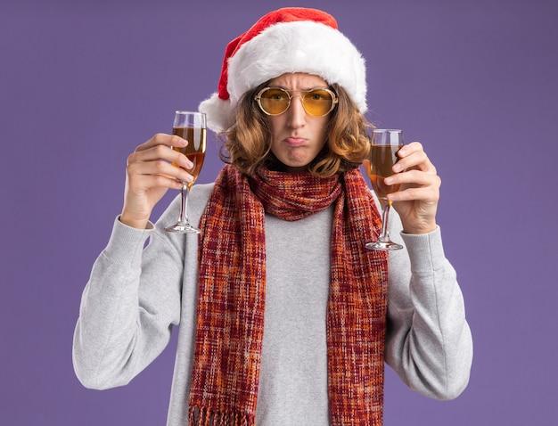 Giovane uomo che indossa il cappello di babbo natale e occhiali gialli con sciarpa calda intorno al collo tenendo bicchieri di champagne guardando la telecamera confuso rendendo la bocca ironica in piedi su sfondo viola