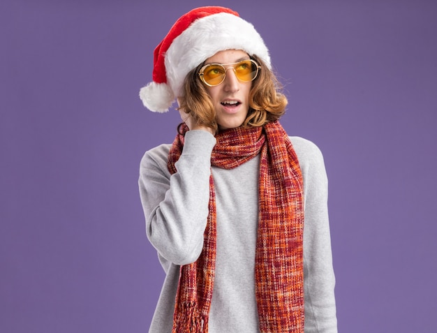 Young man wearing christmas santa hat and yellow glasses with warm scarf around his neck looking up with pensive expression thinking positive standing over purple  wall