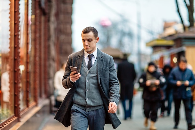 Young man wearing a coat walking down the street and using a cell phone