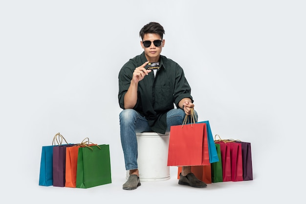 A young man wearing a dark shirt and jeans, carried several bags to go shopping with a credit card