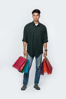 Un giovane che indossa jeans e camicia scura porta molte borse per fare la spesa