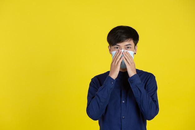 黄色の壁の前に立っている使い捨て医療マスクを身に着けている若い男