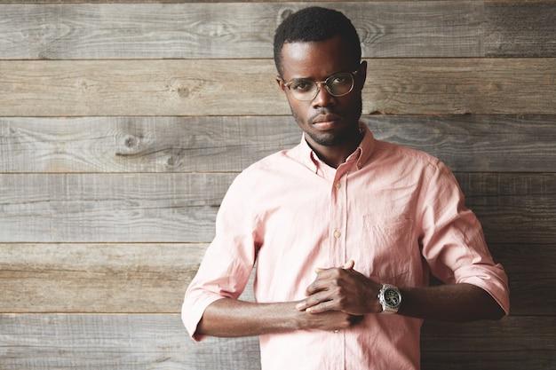 眼鏡とピンクのシャツを着ている若い男