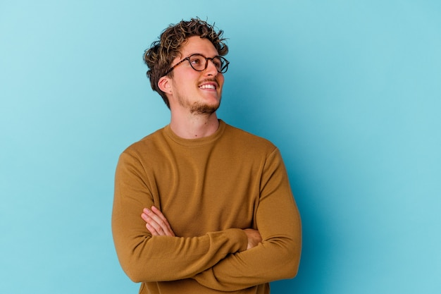 Young man wearing eyeglasses isolated on blue wall dreaming of achieving goals and purposes