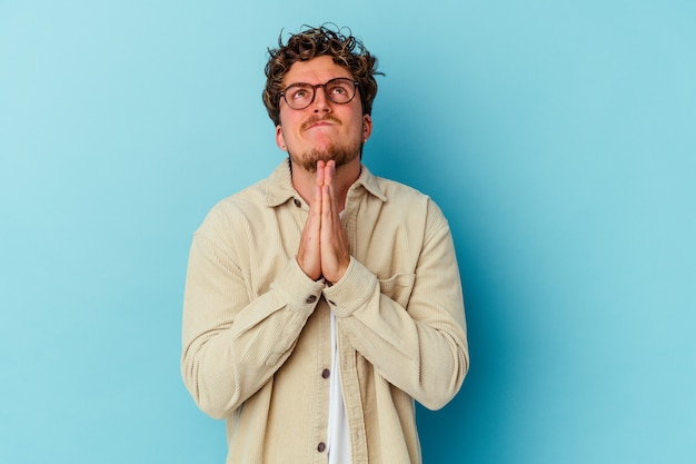 Young man wearing eyeglasses isolated on blue wall holding hands in pray near mouth, feels confident