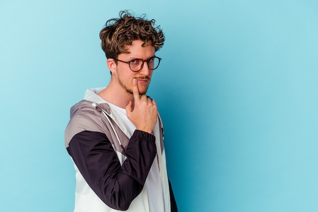 Young man wearing eyeglasses isolated on blue wall unhappy looking in camera with sarcastic expression