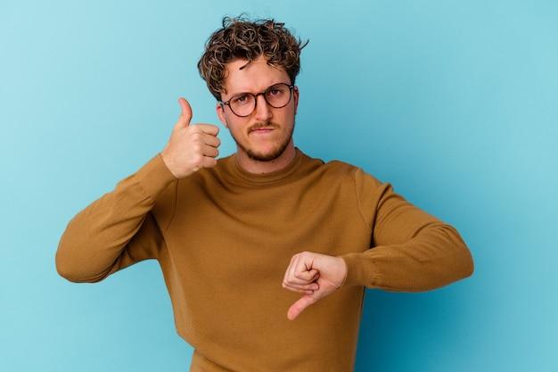 Молодой человек в очках, изолированных на синей стене, показывает палец вверх и палец вниз, сложно выбрать концепцию