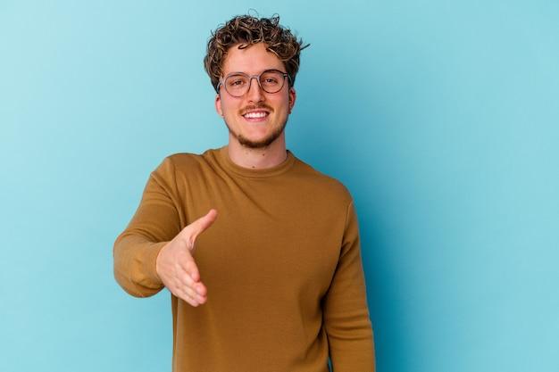 挨拶ジェスチャーでカメラで手を伸ばす青い壁に分離された眼鏡を身に着けている若い男