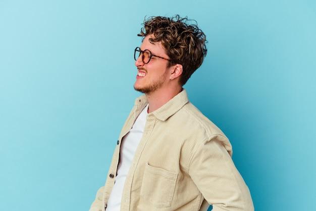 허리 통증을 앓고 파란색 벽에 고립 된 안경을 쓰고 젊은 남자