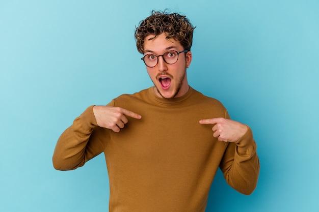 青い壁に隔離された眼鏡をかけている若い男は、指で指して驚いて、広く笑っています。