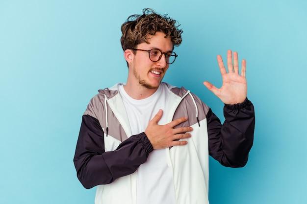 誓いを立てて、胸に手を置いて、青い壁に分離された眼鏡をかけている若い男
