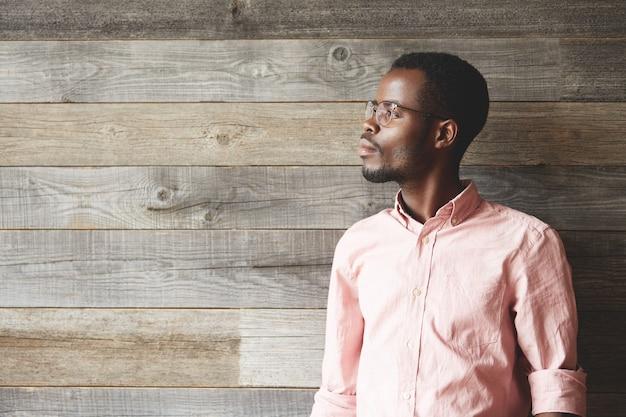 Giovane uomo che indossa occhiali da vista e maglietta rosa
