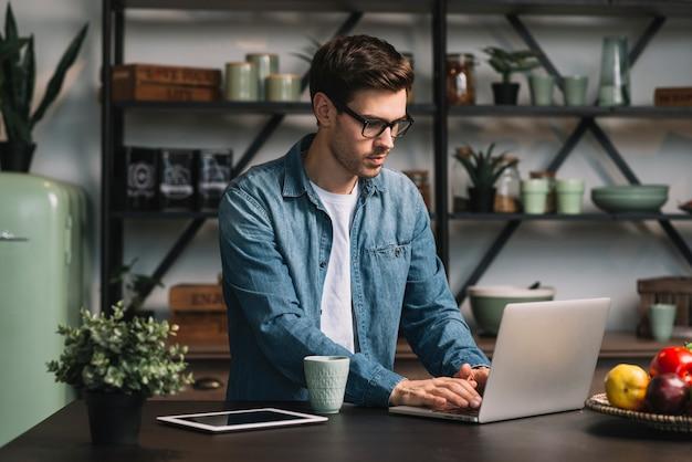 Молодой человек в очках, используя ноутбук на кухне счетчик