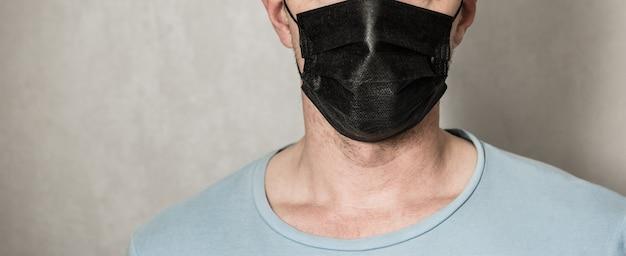 Молодой человек в маске для лица. красивый мужчина в черной толстовке с капюшоном носит черную медицинскую маску, серый фон, копию пространства. концепция карантинного периода пандемии коронавируса covid-19