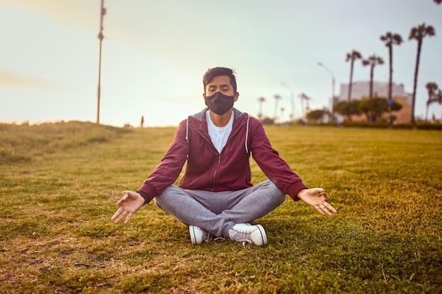 公園でフェイスマスクを身に着けている若い男。日没時のアウトドアスポーツ。公園でのヨガ