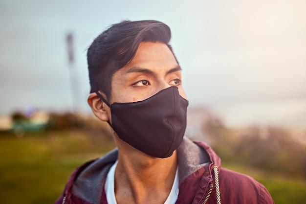 公園でフェイスマスクを身に着けている若い男。日没時のアウトドアスポーツ。 Premium写真
