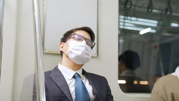 Молодой человек в маске едет в переполненном поезде метро