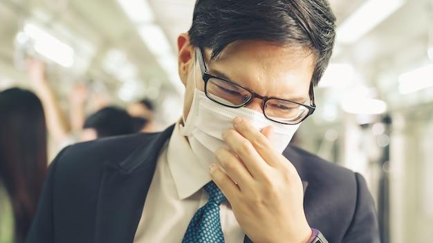 フェイスマスクを身に着けている若い男は混雑した地下鉄の電車で旅行します