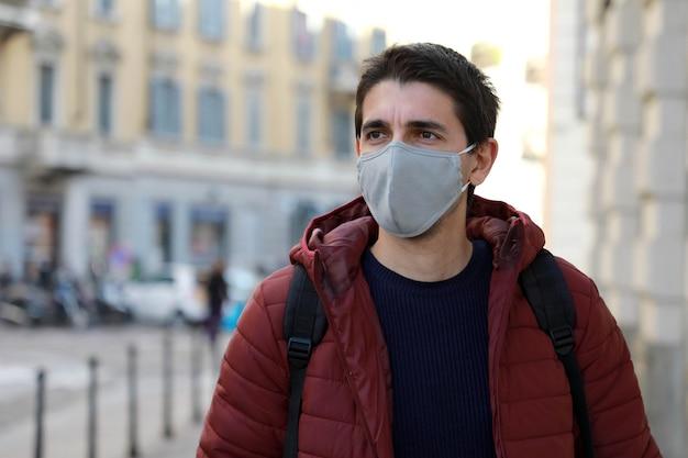横を向いて通りを歩いてフェイスマスクを身に着けている若い男