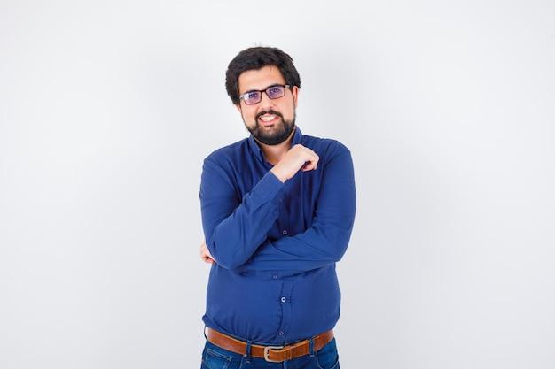 眼鏡をかけ、青いシャツとジーンズでポーズをとって、楽観的な正面図を探している若い男。