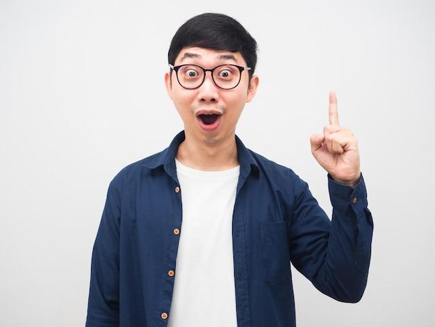 眼鏡をかけている若い男は、いくつかのアイデアが白い背景に指を表示することに驚いています