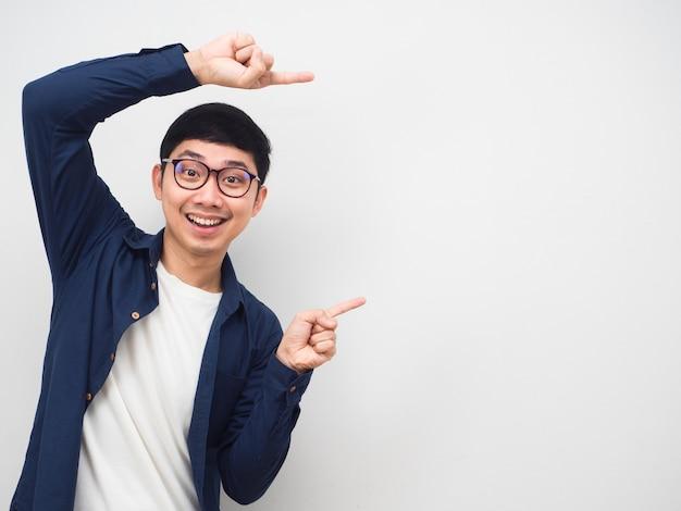 Молодой человек в очках жест указывает пальцем на копию пространства портрет на белом фоне