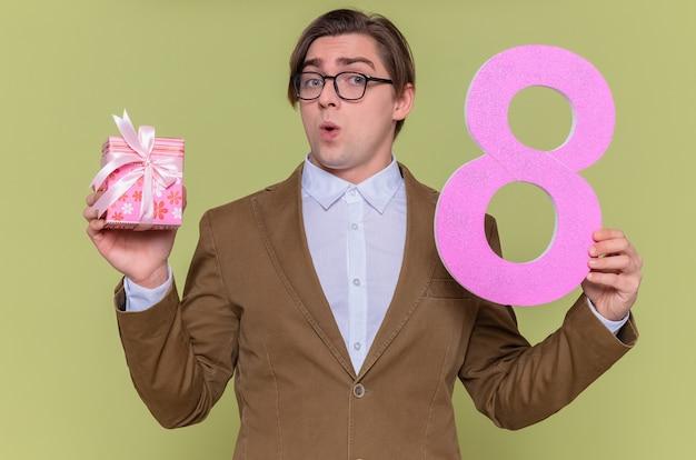 골판지로 만든 숫자 8을 들고 안경을 쓰고있는 젊은 남자가 녹색 벽 위에 서서 행복하고 놀란 국제 여성의 날을보고 있습니다.