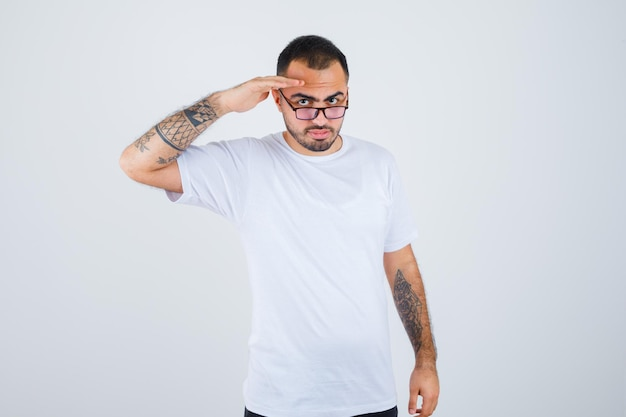 Young man wearing glasses and showing salute gesture in white t-shirt and black pants and looking serious