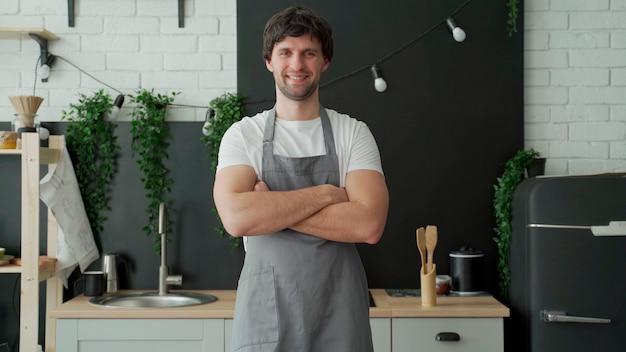 Молодой человек в сером фартуке улыбается и скрещивает руки, стоя на кухне