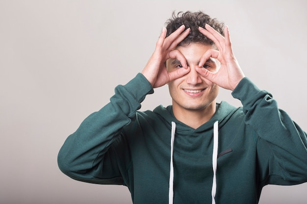 Young man wearing green pullover and holding his hands at his eyes level
