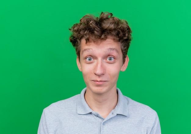 Giovane uomo che indossa la polo grigia con gli occhi spalancati felici e positivi sul verde