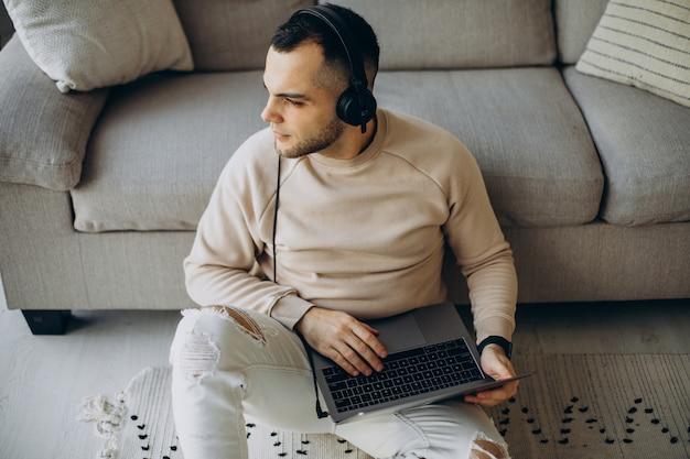 헤드폰을 착용하고 집에서 컴퓨터를 사용하는 젊은 남자