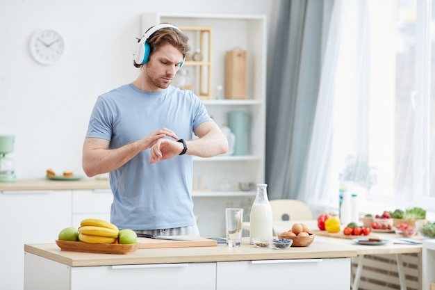 Young man wearing headphones and checking time on his watch while cooking breakfast in the kitchen